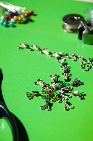 Fashion elements: metal hook and closing eyes on a green background. In the center of the picture are metal hooks in the shape of a flower, in the background there are sewing needles and bobbins. 写真素材