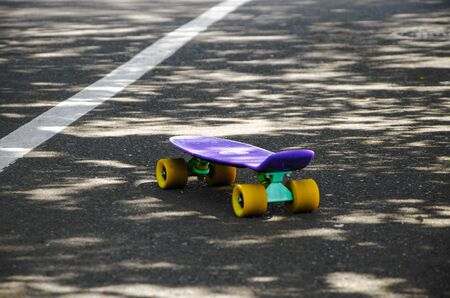 One skateboard on the road. Competitions in extreme sports, a walk in the park, lifestyle. Close-up of a skateboard on asphalt with a dividing line