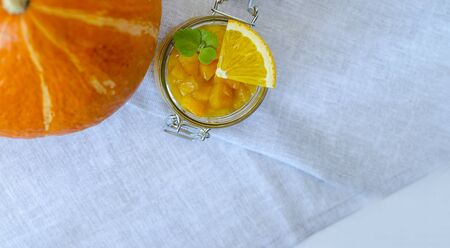 Pumpkin jam or marmalade with orange and lemon. A glass jar of pumpkin jam is decorated with mint leaves. In the center is a whole pumpkin. Close-up. Copy space