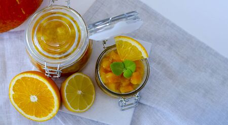Pumpkin jam or marmalade with orange and lemon. In the background is a pumpkin. Two glass jars of pumpkin jam. Still life is decorated with a half of an orange and a half of a lemon. An open jar of jam is decorated with mint leaves. Copy space