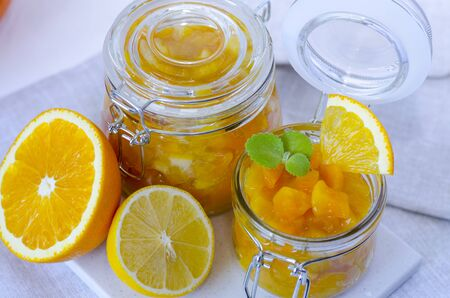Pumpkin jam or marmalade with orange and lemon. Two glass jars of pumpkin jam. Still life is decorated with a half of an orange and a half of a lemon. An open jar of jam is decorated with mint leaves. Copy space