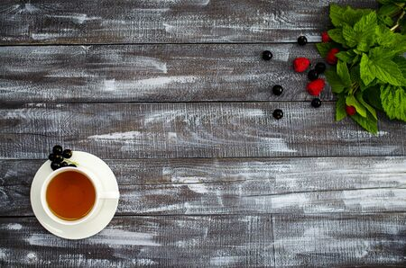 Tea with currant leaves in a cup. On a wooden background, fresh leaves of currant, raspberry and currant. Copy space. Close-up. Standard-Bild - 129467554