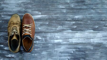 On a wooden background two brown sneakers. One sneaker is new, the other is old. Black Friday - time to throw away old sneakers and buy new ones. Close-up. Copy space. Stok Fotoğraf
