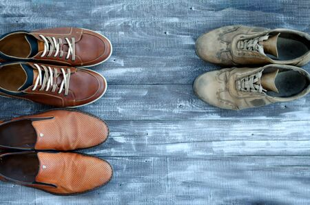 On a wooden background are three pairs of brown shoes. One pair of leather sneakers is very worn, the second is in good condition, the third pair of shoes is new. Black Friday - time to buy new sneakers. Close-up. Copy space