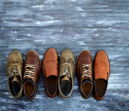 On a wooden background are three pairs of brown shoes. One pair of leather sneakers is very worn, the second is in good condition, the third pair of shoes is new. Shoes are mixed. Black Friday - time to buy new sneakers. Close-up. Copy space