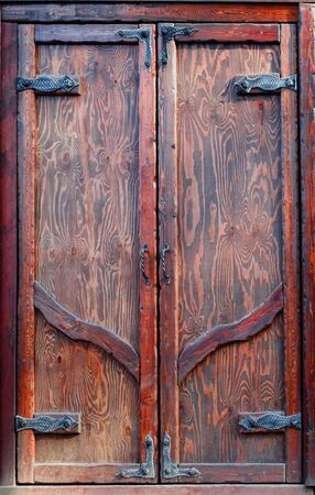 Old wooden mahogany door. Two hinged door leaves. Vintage style. Decorative loops.