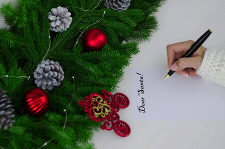Letter to Santa Claus. Christmas decorations and paper with place for greeting. Fir branches are decorated with decorative pine cones and red glass balls and a garland. Girl's hand with a fountain pen writes a letter to Santa Claus. Copy space.