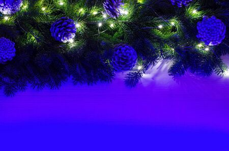 Christmas composition is decorated with a garland, glass balls and decorative pine cones. Bright neon light illuminates the concept. Wood background. Copy space.