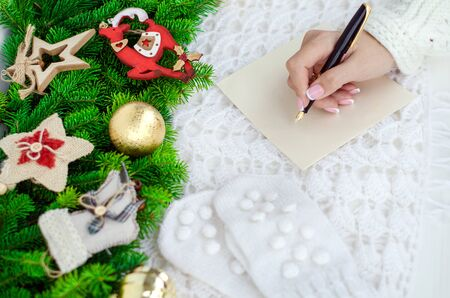 Letter to Santa Claus. Christmas decorations and paper with place for greeting. Fir branches are decorated with decorative pine cones and red glass balls and a garland. Girls hand with a fountain pen writes a letter to Santa Claus. Copy space.