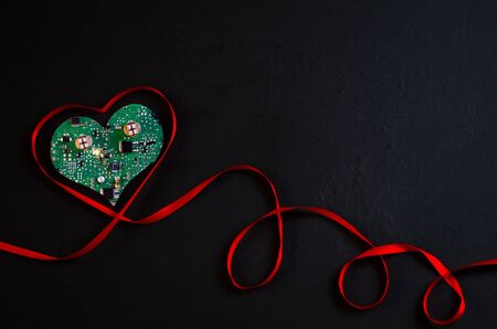Top view of a ribbon shaped like a heart isolated on a black background. In the center of the formed heart an electric circuit with a spark. The concept of caring for each others hearts. Valentines Day Copy space Close-up. Banco de Imagens