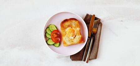Brunch - an egg with sesame seeds on toast, fresh cucumber and tomato. Cutlery lie on a textile napkin. Long banner. Copy space. Top veiw. Reklamní fotografie