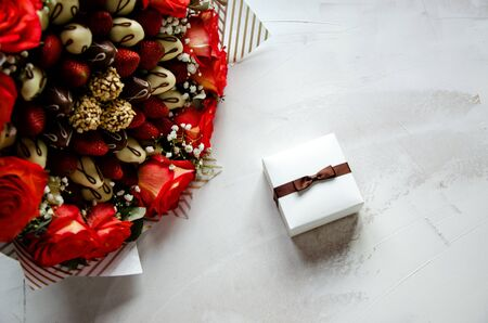 Composition of red-yellow pink flowers, fresh strawberries and fresh strawberries in chocolate on a white background. In the center of the composition, the gift box is tied with a bow. Mother's day greeting card concept, birthday, wedding or other celebration. Close-up. Copy space