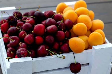 Fresh apricots and cherries in a white wooden box. Half apricots, half cherries. Vegetarian food, supplies. Sale in private gardens. Vitamins Close-up. Copy space.