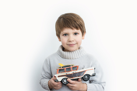 boy in a sweater holding a toy retro car on a white background