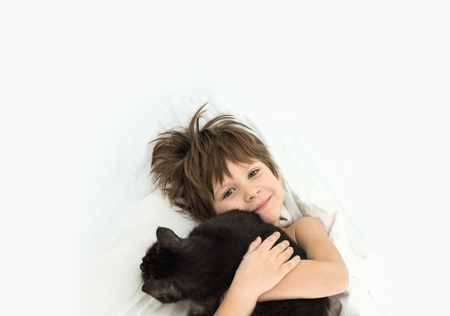 boy with a cat lies in a bed on a white bedclothes. A child of 6 years without a tooth. dropped baby tooth.