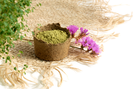 henna powder for dyeing hair and eyebrows and drawing mehendi on hands,  with green  leafs and pink flowers and sackcloth