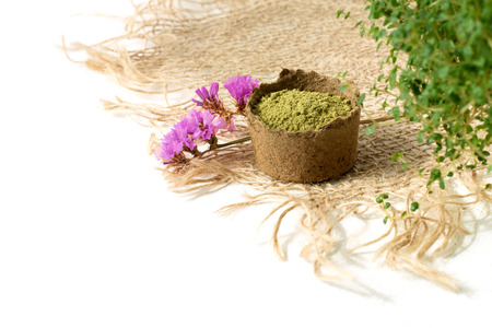 henna powder for dyeing hair and eyebrows and drawing mehendi on hands,  with green  leafs, pink flowers and sackcloth.