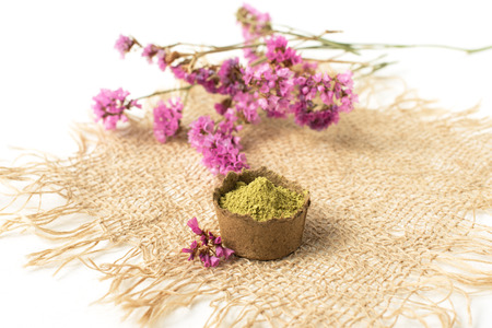 henna powder for dyeing hair, eyebrows and mehendi on a burlap made of natural material l next to pink flowers on a white background, isolate 版權商用圖片