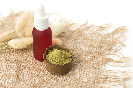 pink cosmetic bottle and henna powder for dyeing hair, eyebrows and mehendi on a burlap made of natural material next to dried flowers on a white background, isolate.