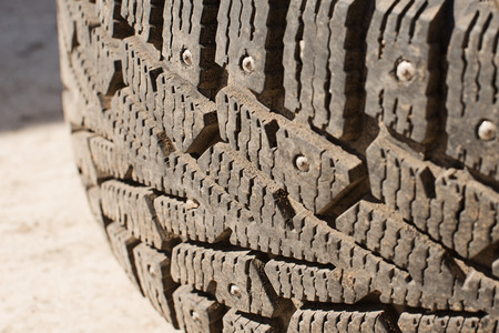 car tires with winter spikes and dirt. replacement of wheels before the new season, steel tool