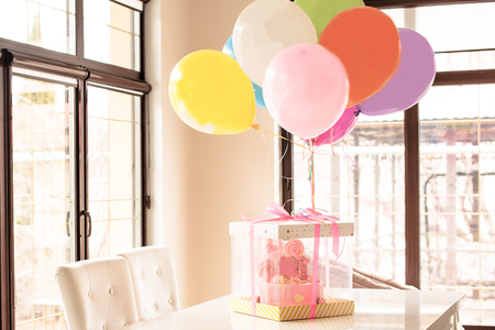 pink cake at the celebration of the first birthday of the girl, balloons  and congratulations 写真素材