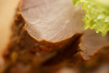 smoked pork meat, turkey with a leaf of green salad, macro shot, close details, meat texture