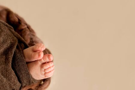feet of the newborn baby, fingers on the foot, maternal care, love and family hugs, tenderness