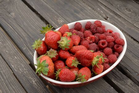 raspberries and strawberries, red berries, in a plate on a dark wooden background.