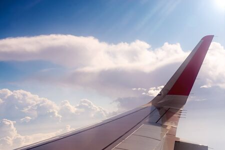 View from the porthole on the wing of plane and clouds. airplane trip Stock Photo