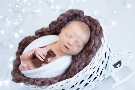 Christmas theme, sleeping newborn baby holding teddy bear, new year eve concept, lights.