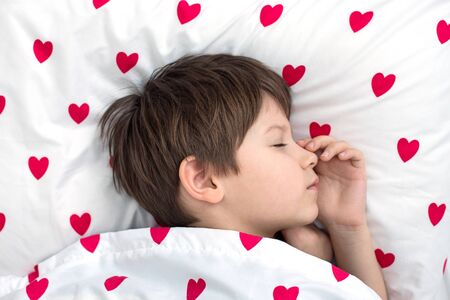the boy is sleeping soundly on white bedding with red hearts. view from above.