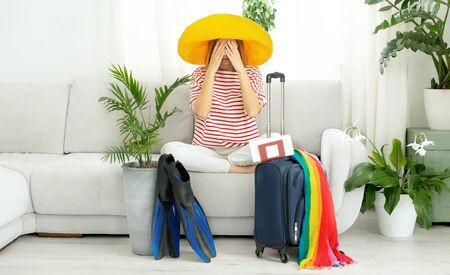 Beautiful girl in a yellow hat stays at home and plans a trip on vacation. Suitcase and flippers for diving. Closing borders and banning flights due to quarantine and COVID-19