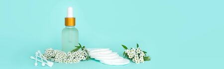 Glass cosmetic bottle with oil. product for women hygiene cotton buds, swab, discs with small white flowers on a turquoise background. Cosmetic jar. Place for text. Stock Photo