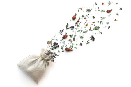 herbal tea, dry plants and flowers, oregano and mint vitamin drink in a linen bag, isolate, place for text, copy space Banque d'images