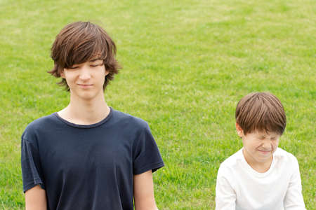 young man with closed eyes and a grin on his face. Green grass lawn. Copy space. Foto de archivo