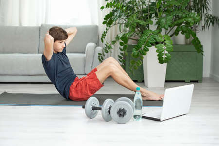 Handsome young man in a dark t-shirt and red shorts does sports at home online. Teenager is training in the room