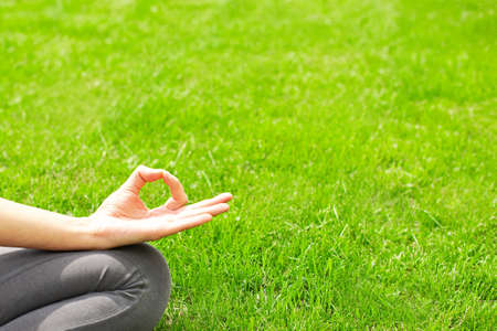 A woman practices yoga outdoors on the grass. Copy space