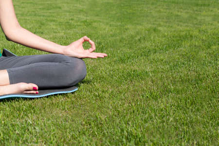 A woman practices yoga outdoors on the grass. Bental health, anxiety reduction, inner peace