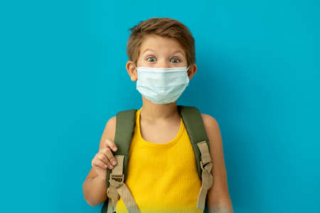 Schoolboy in a medical mask with a backpack. Back to school. Copy space. Blu background