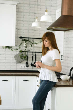 A girl is standing in profile in jeans and a white T-shirt is drinking coffee in a white kitchen in a Scandinavian house. Cozy scene, Hygge concept Banco de Imagens