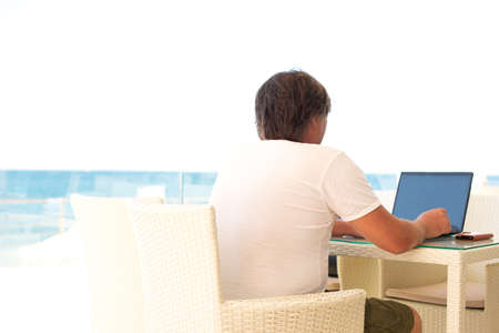 Workplace in a cafe with a sea view. Man working on a laptop in a cafe. Copy space, Mock up. people from behind