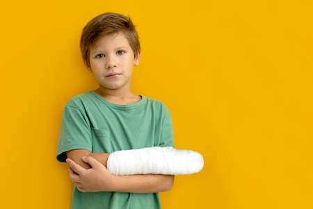 A child with a plaster on his hand. Broken arm. Yellow background. Copy space Standard-Bild