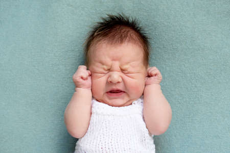 portrait of crying newborn baby. emotions of discontent. colic