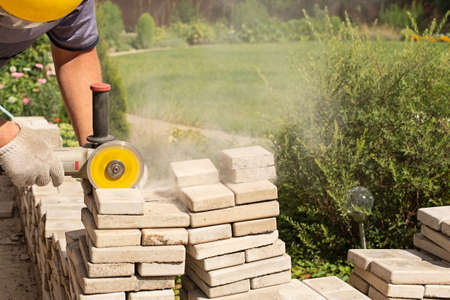 Master saws paving slabs with a grinder grinder. Dust