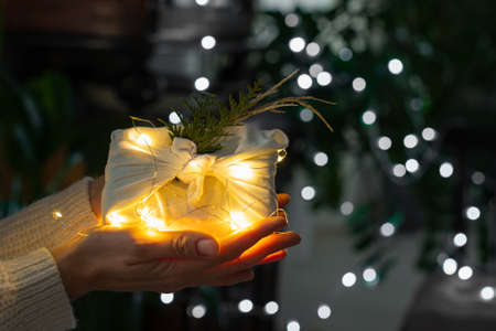 Christmas gift in hands. Packaging in eco-friendly materials, furoshiki fabric. Bokeh, selective focus