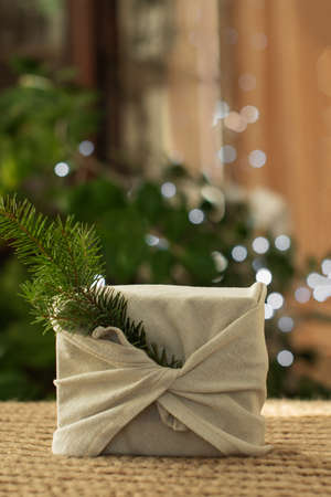 Christmas gift. Vertical. Packaging in eco-friendly materials, furoshiki fabric. Bokeh, selective focus. High quality photo