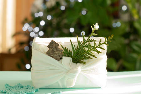 Christmas gift. Packaging in eco-friendly materials, furoshiki fabric. Bokeh, selective focus. High quality photo