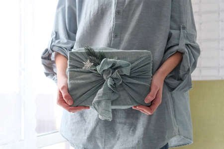 wrapping gifts in fabric for Christmas in furoshiki style. Eco friendly concept. DIY