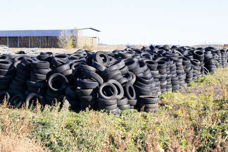Industrial landfill for the processing of waste tires and rubber tires. Pile of old tires and wheels for rubber recycling. Tire dump