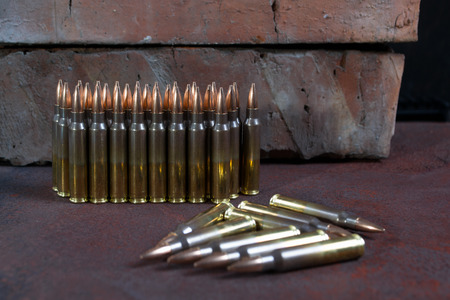 Group of  ammunition geometrically placed in rows on a rusted metal background Stock Photo